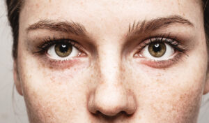 close-up-of-womans-face-with-freckles-eyebrows-eyes