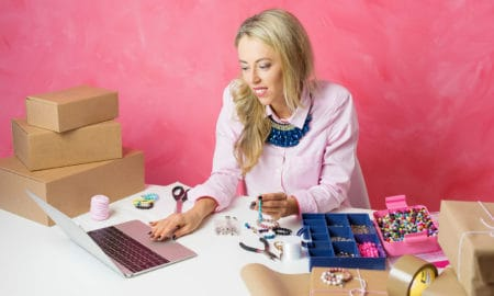 Woman working from home. Making pieces of jewellery and sells them online.