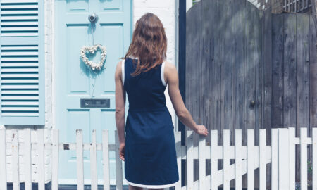 woman-in-blue-dress-looking-at-house-with-blue-door