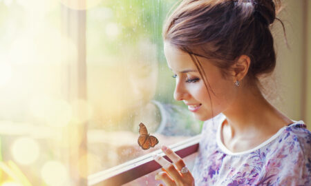 woman-looking-through-a-window-at-a-butterfly