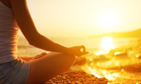 woman-sitting-on-beach-meditating