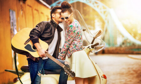 woman-and-man-flirting-while-man-sits-on-a-scooter-holding-a-guitar