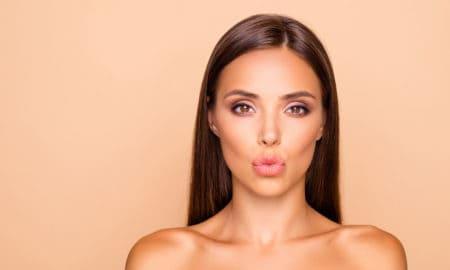 Adorable charming brunette hair lady with her naked shoulders she send kiss look at camera isolated on pastel beige background with copy space for text