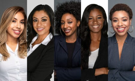 Group of six happy minority businesswomen at work