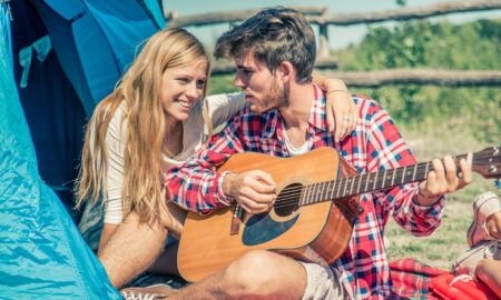 young-love-young-couple-camping-while-man-plays-guitar