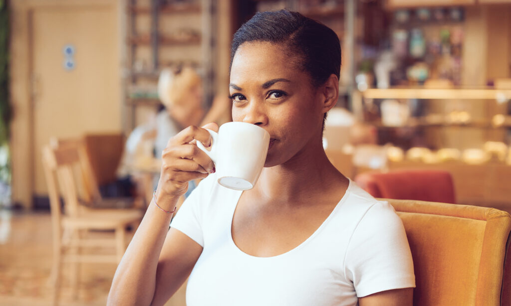 woman-smiling-and-drinking-coffee