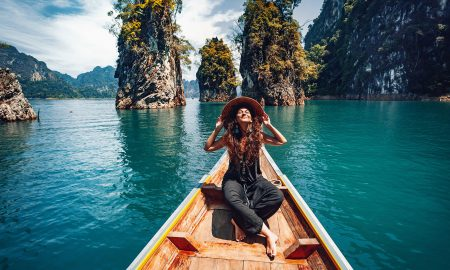 happy young woman tourist in asian hat on the boat at lake