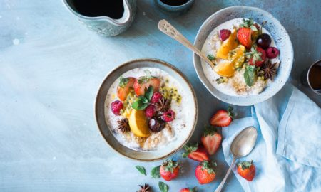 two small bowls of oatmeal topped with oranges, grapes, berries, seeds, and green leaves beside are 7 slices of strawberries, spoon, and blue cloth blue background, starchy foods for a slim body, Starchy Foods You can Eat to Stay Slim
