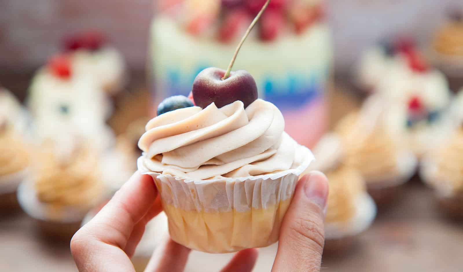 Cheesecake cupcake with cream cheese frosting and fresh cherry o