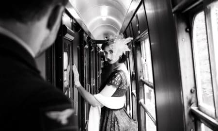 Portrait of beautiful woman in vintage tea dress standing in corridor of locomotive train as air force officer in uniform watches her