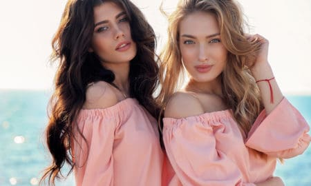 fashion photo of two beautiful girls in casual clothes posing outdoor
