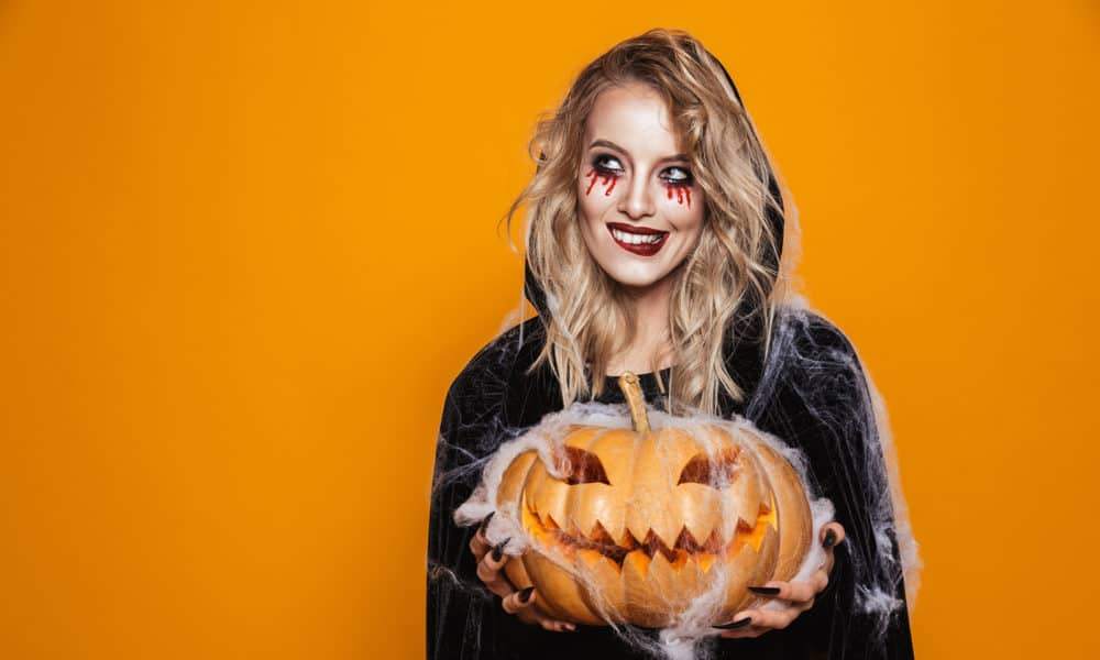 European witch woman wearing black costume and halloween makeup