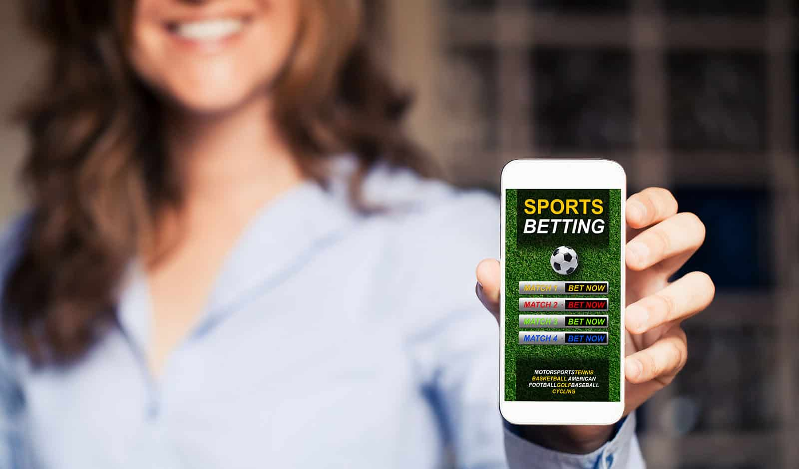 Smiling woman holding a mobile phone with sports betting website