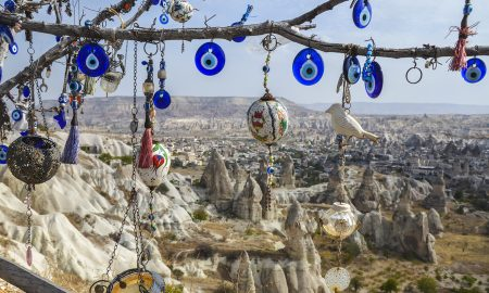 evil-eye-necklaces-hanging-from-tree-in-desert