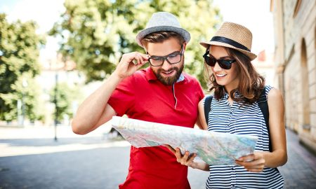 Young couple on vacation looking at map outdoors