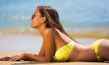 brunette woman yellow bikini sea