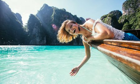 beautiful-woman-leaning-over-boat-in-tropical-location