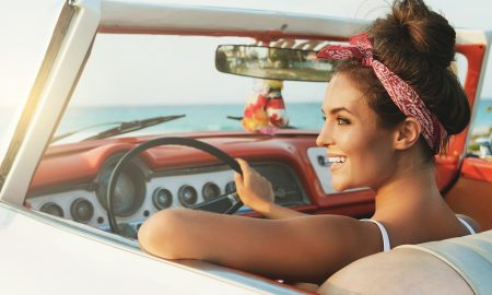 Beautiful and happy woman inside a retro car