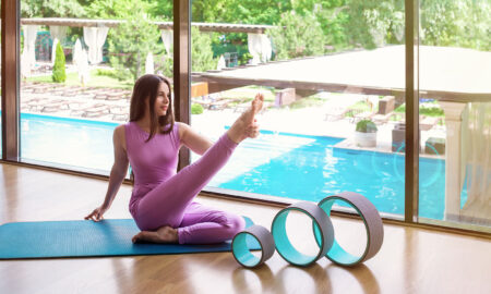 why-you-needna-yoga-wheel-woman-sitting-in-home-stretching-leg-with-yoga-wheels-in-front-of-her