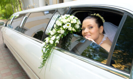 book-a-limousine-or-party-bus-for-your-wedding-bride-looking-out-of-white-limo-on-wedding-day