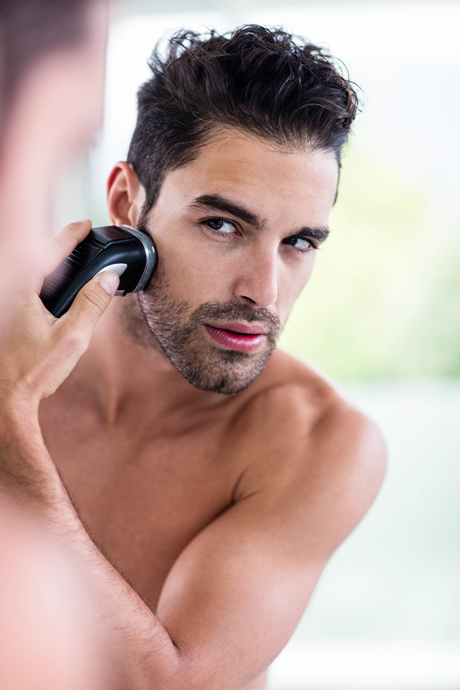 reasons-men-should-use-body-grooming-devices-man-looking-in-mirror-while-shaving