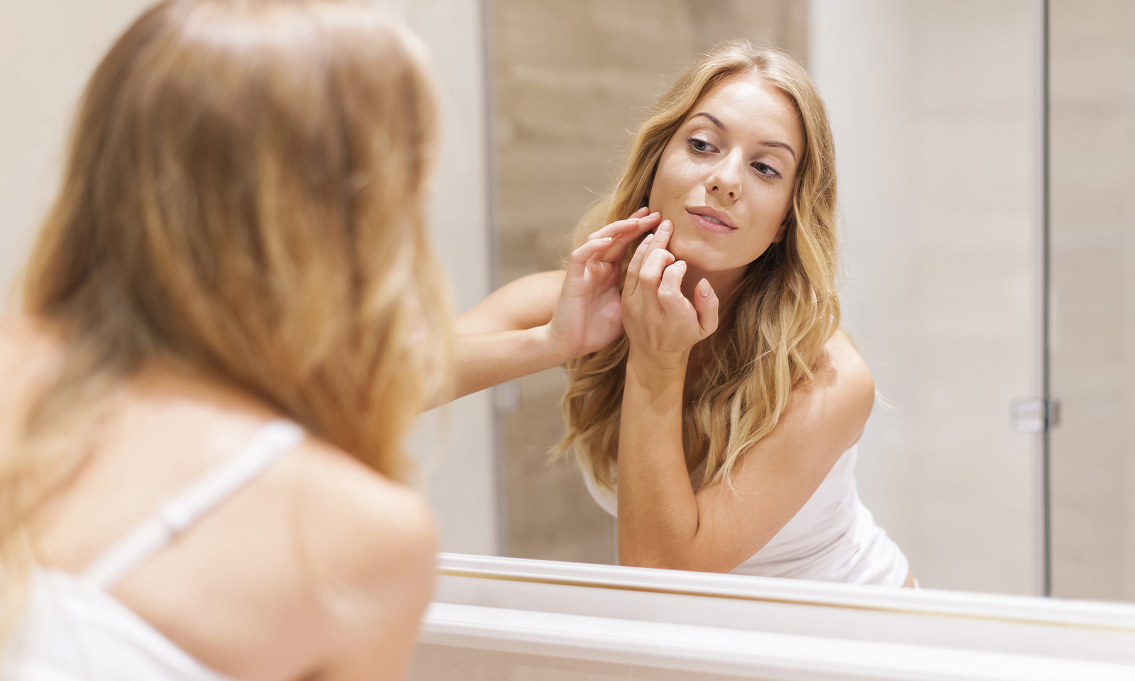 the-right-way-to-wash-your-face-to-avoid-skin-complications-woman-touching-face-in-mirror