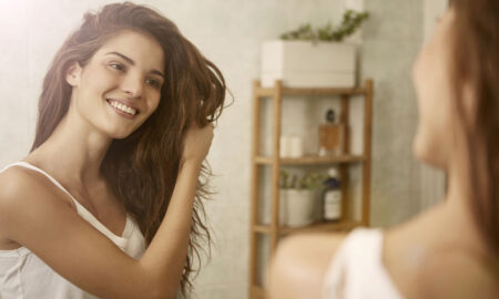 tips-for-healthy-hair-woman-looking-at-reflection-touching-hair
