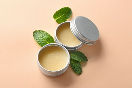 Containers with lemon balm salve and leaves on  light background